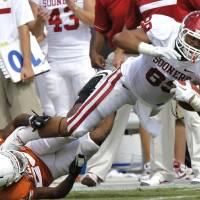 Photo - Oklahoma's Austin Haywood (89) is brought down by Texas' Carrington Byndom (23) during the Red River Rivalry college football game between the University of Oklahoma Sooners (OU) and the University of Texas Longhorns (UT) at the Cotton Bowl in Dallas, Saturday, Oct. 8, 2011. Photo by Chris Landsberger, The Oklahoman  ORG XMIT: KOD