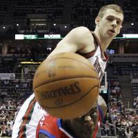 Photo -   Philadelphia 76ers' Jrue Holiday and Milwaukee Bucks' Jon Leuer go after a loose ball during the first half of an NBA basketball game, Wednesday, April 25, 2012, in Milwaukee. (AP Photo/Morry Gash)