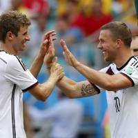Photo - Germany's Thomas Mueller, left, is greeted by Lukas Podolski after being substituted after scoring a hat-trick during the group G World Cup soccer match between Germany and Portugal at the Arena Fonte Nova in Salvador, Brazil, Monday, June 16, 2014.  (AP Photo/Matthias Schrader)