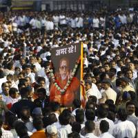 Photo -   FILE - In this Nov. 18, 2012 file photo, Indian mourners carry a poster of Hindu hardline Shiv Sena party leader Bal Thackeray with the words