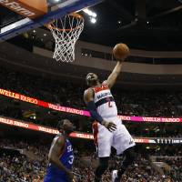 Photo - Washington Wizards' John Wall, right, dunks the ball as Philadelphia 76ers' Henry Sims looks on during the first half of an NBA basketball game, Saturday, March 1, 2014, in Philadelphia. (AP Photo/Matt Slocum)