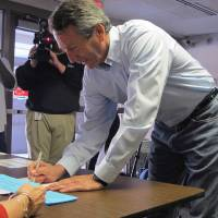 Photo - Former South Carolina Gov. Mark Sanford signs in before voting in Charleston, S.C., on Tuesday, April 2, 2013. Sanford is facing former Charleston County councilman Curtis Bostic in the Republican runoff for South Carolina's vacant 1st District congressional seat.  (AP Photo/Bruce Smith)