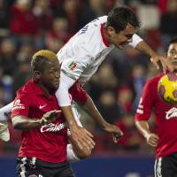 Photo - Tijuana's Duvier Riascos, left, fights for the ball with Toluca's Edgar Duenas during a Mexican soccer league match in Tijuana, Mexico, Thursday, Nov. 29, 2012. (AP Photo/Christian Palma)