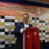 Photo - Newly-appointed Serbian national soccer team coach Dick Advocaat poses for photographers with a  Serbian jersey  during a press conference in Stara Pazova, Serbia, Monday, July 28, 2014. Advocaat signed a two-year contract with Serbia and has the mandate to lead them to the 2016 European Championship in France. (AP Photo/Darko Vojinovic)