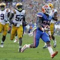 Photo -   Florida running back Mike Gillislee, right, runs to the end zone on a 12-yard touchdown play past LSU defensive tackle Ego Ferguson (9) and linebacker Lamin Barrow (57) during the second half of an NCAA college football game, Saturday, Oct. 6, 2012, in Gainesville, Fla. (AP Photo/John Raoux)