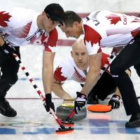 Photo - Canada's Ryan Fry delivers the rock while Ryan Harnden, left, and E.J. Harnden, right, sweep the ice during the men's curling match against the United States at the 2014 Winter Olympics, Sunday, Feb. 16, 2014, in Sochi, Russia. (AP Photo/Wong Maye-E)