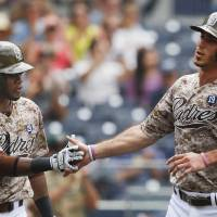 Photo - San Diego Padres' Tommy Medica, right, is congratulated by Irving Falu after scoring against the Arizona Diamondbacks on a sacrifice fly by Alexi Amarista during the fourth inning of a baseball game  Sunday, June 29, 2014, in San Diego.  (AP Photo/Lenny Ignelzi)