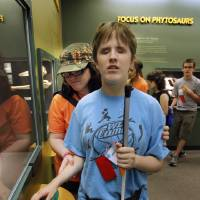 Photo - Brittany Donley's hand is guided to an exhibit Wednesday by volunteer Kim McCall as campers with Oklahomans Without Limits tour the Sam Noble Museum of Natural History in Norman. PHOTOS BY STEVE SISNEY, THE OKLAHOMAN