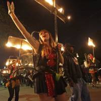 Photo - Members of the all-female flambeaux group, called 'Glambeaux,' march in the Krewe of Muses Mardi Gras parade in New Orleans, Thursday, Feb. 27, 2014. (AP Photo/Gerald Herbert)