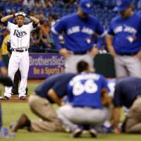Photo - Tampa Bay Rays' Desmond Jennings reacts while medical personnel attend to Toronto Blue Jays starting pitcher J.A. Happ after during the second inning of a baseball game Tuesday, May 7, 2013, in St. Petersburg, Fla. Happ was hit by a line drive off of Jennings' bat. (AP Photo/Mike Carlson)