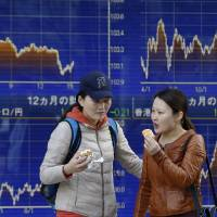Photo - Women eat ice cream in front of an electronic stock price indicator in Tokyo Monday, April 7, 2014. Internet and technology stocks tumbled across Asia on Monday as a sell-off spread from Wall Street where investors knocked down such companies over worries about excessively high valuations. (AP Photo/Shizuo Kambayashi)