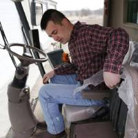 Photo - Nick Guetterman folds a seat as he climbs into a combine on his farm near Bucyrus, Kan., Wednesday, Feb. 19, 2014.  Farmers from across the nation gathered in Washington this month for their annual trek to seek action on the most important matters in American agriculture.  But this time, a new issue emerged: growing unease about how the largest seed companies are gathering vast amount of data from sensors on tractors, combines and other farm equipment. The sensors measure soil conditions, seeding rates, crop yields and many other variables.  (AP Photo/Orlin Wagner)