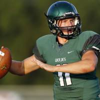 Photo - Edmond Santa Fe's Justice Hansen (11) passes against Norman North during a football scrimmage at Edmond Santa Fe High School in Edmond, Okla., Thursday, Aug. 22, 2013. Photo by Nate Billings, The Oklahoman