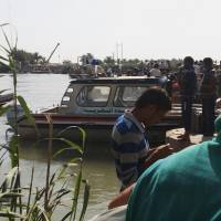 Photo - Fallujah residents bring fuel from Baghdad, as they cross the Euphrates river in Fallujah, 40 miles (65 kilometers) west of Baghdad, Iraq, Sunday, June 22, 2014. Sunni militants have seized another town in Iraq's western Anbar province, the fourth to fall in two days, officials said Sunday, in what is shaping up to be a major offensive in one of Iraq's most restive regions. (AP Photo)