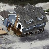 Photo - This aerial photo shows a collapsed house along the central Jersey Shore coast on Wednesday, Oct. 31, 2012. New Jersey got the brunt of Sandy, which made landfall in the state and killed six people. More than 2 million customers were without power as of Wednesday afternoon, down from a peak of 2.7 million. (AP Photo/Mike Groll) ORG XMIT: NJMG117