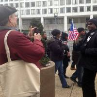 Photo - Curator William Pretzer takes a photograph of Larry Holmes, 56, of Washington with his Obama inauguration flag Monday, Jan. 21, 2013, at the inauguration in Washington. Pretzer, a curator from the Smithsonian National Museum of African American History and Culture, was asking for objects to be donated for future exhibitions. The Smithsonian's National Museum of African American History and Culture will open its doors during President Barack Obama's second term with a large display about the first black president. (AP Photo/Brett Zongker)