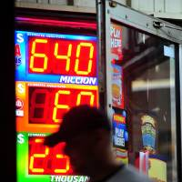 Photo -   A customer walks out of the Riverside Travel Center in Hilton, Ga., late Friday night after purchasing a lottery ticket for the Mega Millions Lottery which reached an estimated jackpot of $645 million for Friday night's drawing. (AP Photo/Jay Hare, The Eagle)