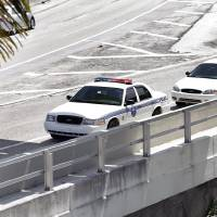 Photo -   A City of Miami police officer stands watch near the scene where a naked man, far right, was shot dead on the MacArthur Causeway ramp onto Northeast 13th Street in Miami on Saturday, May 26, 2012. A witness said the naked man continued to chew on the face of another naked man on a Miami highway ramp and growled when a police officer tried to stop him. The victim remained hospitalized Monday. (AP Photo/The Miami Herald, Marsha Halper) MAGS OUT