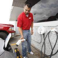 Photo - Hudiburg Nissan salesman Eddie Morris demonstrates how to plug in the all-electric Nissan Leaf. Photo by PAUL HELLSTERN, The Oklahoman