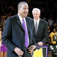 Photo - Los Angeles Lakers general manager Mitch Kupchak, right, holds the No. 52 jersey of former Laker Jamaal Wilkes during a jersey retirement ceremony at halftime of an NBA basketball game between the Lakers and the Portland Trail Blazers, Friday, Dec. 28, 2012, in Los Angeles. (AP Photo/Alex Gallardo)