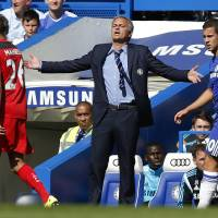 Photo - Chelsea's manager Jose Mourinho, center, gestures as he watches his team play against Leicester City during their English Premier League soccer match at Stamford Bridge, London, Saturday, Aug. 23, 2014. (AP Photo/Sang Tan)