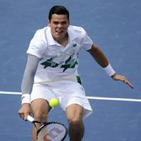 Photo - Milos Raonic, of Canada, returns the ball against Donald Young during a match at the Citi Open tennis tournament, Saturday, Aug. 2, 2014, in Washington. Raonic won the match 6-4, 7-5. (AP Photo/Nick Wass)