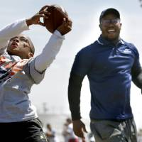Photo - James White catches a pass as Denver Broncos' Von Miller looks on during the Wes Welker pro camp at Douglass High School in  Oklahoma City., Saturday, April 05, 2014. Photo by Sarah Phipps, The Oklahoman