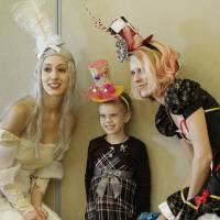 Photo - Isabella Baxter, 5, poses with Melissa Meyers, left, and Sarah White at the Mad Hatter Tea Party in Edmond.