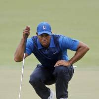 Photo - Tiger Woods lines up his shot on the first hole as rain starts to fall during the first round of the Cadillac Championship golf tournament Thursday, March 6, 2014, Fla. (AP Photo/Marta Lavandier)