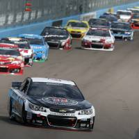 Photo - Kevin Harvick leads a group of cars into Turn 1 during the NASCAR Sprint Cup Series auto race Sunday, March 2, 2014, in Avondale, Ariz. (AP Photo/Ross D. Franklin)
