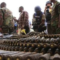 Photo - FILE In this Wednesday, June 5, 2013 file photo, journalists look at arms and ammunition which military commanders say they seized from Islamic fighters, in Maiduguri, Nigeria, on Wednesday, June 5, 2013. Boko Haram, the radical group that once attacked only government institutions and security forces, is increasingly targeting civilians. Some 155,000 square kilometers (60,000 square miles) of Nigeria are now under a state of emergency. On Friday, June 21, 2013, villagers streamed into Maiduguri from the Gwoza hills, saying Boko Haram fighters were threatening a bloodbath in the area where they appear to have regrouped, scrubby mountains with rock caves some 150 kilometers (90 miles) from the city. (AP Photo/Jon Gambrell, File)