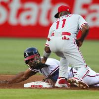 Photo - Atlanta Braves Jason Heyward, left, is tagged out attempting to steal second base by Philadelphia Phillies shortstop Jimmy Rollins, right, in the third inning of a baseball game Monday, June 16, 2014, in Atlanta. (AP Photo/Todd Kirkland)