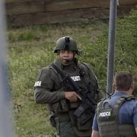 Photo - A police officer holds a rifle as he walks near the scene where a man is said to be holding four Gwinnett County firefighters hostage in Suwanee, Ga., Wednesday, April 10, 2013. (AP Photo/John Bazemore)