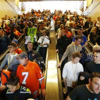 Photo - Football fans make their way to trains on Sunday, Feb. 2, 2014, in Secaucus, N.J. The Seattle Seahawks are scheduled to play the Denver Broncos in NFL football's Super Bowl XLVIII game on Sunday evening at MetLife Stadium in East Rutherford, N.J. (AP Photo/Matt Rourke)