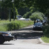 Photo - Law enforcement officials block the street to the scene in Oakland Township, Mich., Monday, June 17, 2013 where officials search for the remains of Teamsters union president Jimmy Hoffa who disappeared from a Detroit-area restaurant in 1975. (AP Photo/Carlos Osorio)