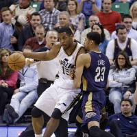 Photo - New Orleans Pelicans' Anthony Davis (23) defends against Utah Jazz's Derrick Favors (15) in the first quarter during an NBA basketball game on Friday, April 4, 2014, in Salt Lake City. (AP Photo/Rick Bowmer)