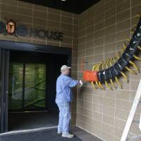 Photo - Exhibitry artist Mark Van Wickler polishes his centipede sculpture at the Houston Zoo's new bug house Friday, May 23, 2014, in Houston. The Bug House, opening this weekend, has 30 species of native and exotic insects on display. (AP Photo/Pat Sullivan)