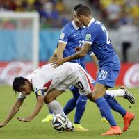 Photo - Costa Rica's Bryan Ruiz, left, is challenged by Greece's Jose Holebas during the World Cup round of 16 soccer match between Costa Rica and Greece at the Arena Pernambuco in Recife, Brazil, Sunday, June 29, 2014. (AP Photo/Ricardo Mazalan)