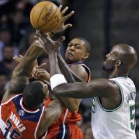 Photo -   CORRECTS ID OF WIZARDS PLAYER AT MIDDLE TO BRADLEY BEAL, INSTEAD OF A.J. PRICE - Washington Wizards forward Trevor Booker (35) and guard Bradley Beal, middle, vie for a loose ball with Boston Celtics forward Kevin Garnett (5) during the first half of an NBA basketball game in Boston on Wednesday, Nov. 7, 2012. (AP Photo/Elise Amendola)