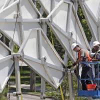 Photo - The 36-foot-tall arch that is one of the most recognizable symbols left from the 2002 Winter Olympics is being moved off the University of Utah campus Friday, Aug. 1, 2014, in Salt Lake City. The city became the new caretaker of the arch this week after it was dismantled into 4,000 pieces by the University of Utah at a cost of $116,000. The arch had stood the last 11 years outside Rice-Eccles Stadium after being downtown during the Olympic games, where it graced the medals plaza. (AP Photo/Rick Bowmer)