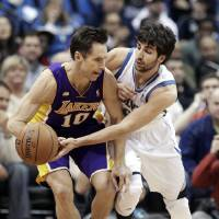 Photo - Minnesota Timberwolves' Ricky Rubio of Spain, right, pressures Los Angeles Lakers' Steve Nash in the first quarter of an NBA basketball game Wednesday, March 27, 2013 in Minneapolis. Rubio was called for a foul on the play. (AP Photo/Jim Mone)