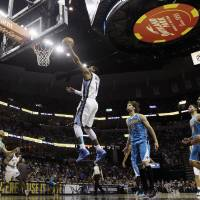 Photo - Memphis Grizzlies' Mike Conley (11) goes to the basket in front of New Orleans Hornets' Robin Lopez (15) during the first half of an NBA basketball game in Memphis, Tenn., Saturday, March 9, 2013. (AP Photo/Danny Johnston)