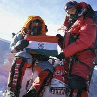 Photo - In this Sunday, May 25, 2014 handout photo, Malavath Poorna, left, holds up her nation's flag on Mount Everest, Nepal. A social charity says the 13-year-old daughter of poor Indian farmers has become the youngest girl to climb Mount Everest. Poorna says she and a team of Nepalese climbing guides made it to the top on May 25 from the northern side in Tibet. (AP Photo/Andhra Pradesh Information Center)