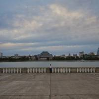 Photo - In this Thursday, Sept. 13, 2012 photo, a woman stands along the bank of the Taedong River at the end of the day in Pyongyang, North Korea. (AP Photo/David Guttenfelder)