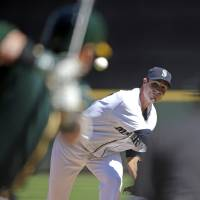 Photo - Seattle Mariners starting pitcher Chris Young throws against the Oakland Athletics in the first inning of a baseball game Sunday, April 13, 2014, in Seattle. (AP Photo/Elaine Thompson)