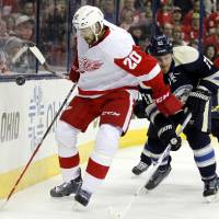 Photo - Detroit Red Wings' Drew Miller, left, works for the puck against Columbus Blue Jackets' James Wisniewski  in the first period of an NHL hockey game in Columbus, Ohio, Tuesday, March 25, 2014. (AP Photo/Paul Vernon)