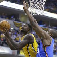 Photo -  Indiana Pacers guard Lance Stephenson, left, shoots under Oklahoma City Thunder forward Serge Ibaka in the second half of an NBA basketball game in Indianapolis, Sunday, April 13, 2014. The Pacers defeated the Thunder 102-97. (AP Photo/Michael Conroy)