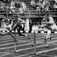 Photo -   File- This July 26, 1952 file photo shows Milt Campbell, center, of Plainfield, N.J. getting set to clear the final hurdle to make him the winner in the fifth heat of the 110-meter hurdles event in the Olympic decathlon at Helsinki, Finland. Campbell, who became the first black to win the Olympic decathlon in 1956 and went on to play professional football and become a motivational speaker, died Friday Nov. 2, 2012 after a battle with prostate cancer. He was 78. (AP Photo/File)