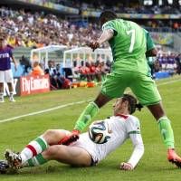 Photo - Iran's Andranik Teymourian slides under Nigeria's Ahmed Musa to take the ball away during the group F World Cup soccer match between Iran and Nigeria at the Arena da Baixada in Curitiba, Brazil, Monday, June 16, 2014.  (AP Photo/Jon Super)