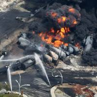 Photo - In this Saturday, July 6, 2013 photo, smoke rises from railway cars carrying crude oil after derailing in downtown Lac Megantic, Quebec. Lac-Megantic still struggles to recover as it marks the disaster's one-year anniversary. (AP Photo/The Canadian Press, Paul Chiasson)